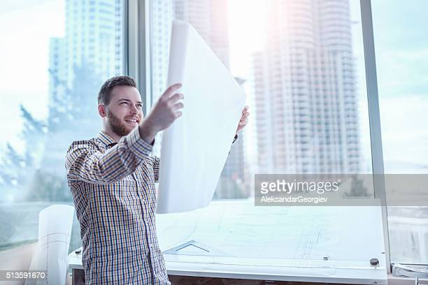Smiling Architect Analyzing Blueprint Plans in His Office
