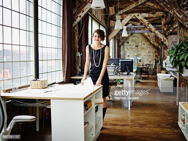 Smiling architect reviewing plans in office