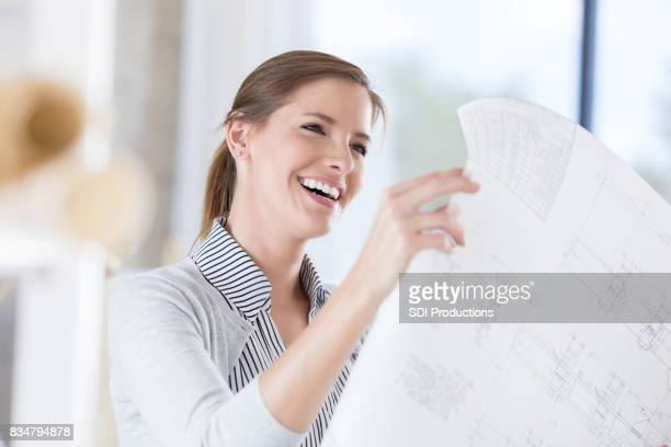 Smiling architect reviews finished blueprint