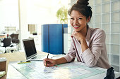 Smiling young Asian architect sitting alone at her desk in a modern office working on a building design