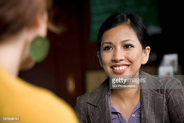 Smiling Asian Business Woman Talking to Her Associate