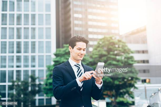 Smiling asian businessman using smart phone in front of skyscrapers