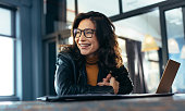 Woman sitting at the desk with laptop looking away and smiling. Asian woman in casuals at office.