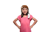 Smiling asian child in aviator helmet standing isolated over white background