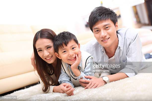smiling asian family, looking at the camera.