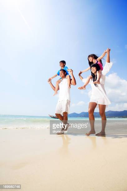 Smiling Asian family walking on the beach.
