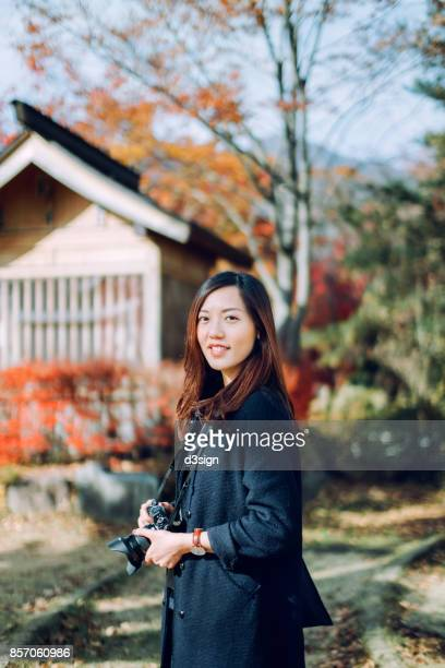Smiling Asian female traveller taking pictures of beautiful Autumn foliage with camera in park