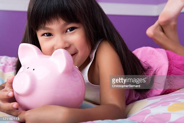 Smiling asian girl holding piggy bank