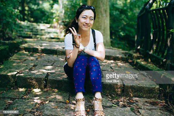 Smiling asian girl sitting on the ground
