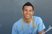 Smiling Asian male nurse with copy space on the left.