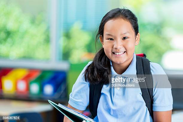Smiling Asian private schoolgirl before class