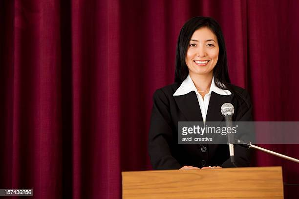 Smiling Asian Woman at Podium