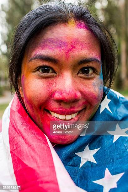 Smiling Asian woman covered in pigment powder wearing American flag