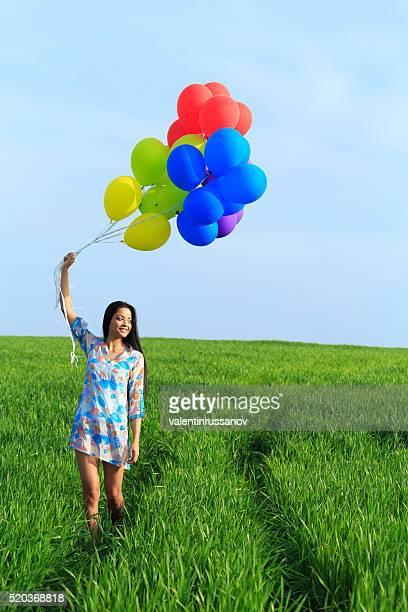 Lächelnde asiatische Frau hält Luftballons und genießen Sie den Sommer