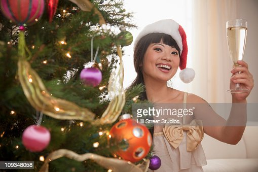 Smiling Asian woman next to Christmas tree drinking Champagne