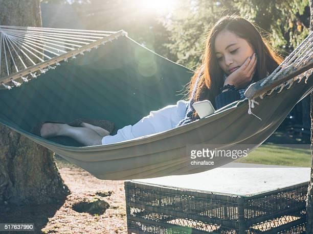Sorridente Donna asiatica rilassante su amaca con cellulare