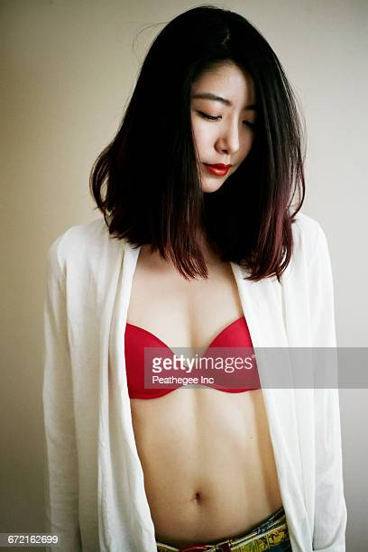 Smiling Asian woman standing at wall wearing red bra