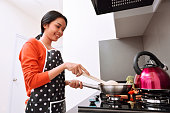 Smiling asian woman using frying pan and cooking in the kitchen