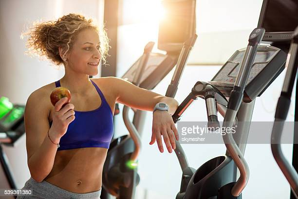 Smiling athletic woman holding an apple and relaxing in gym.