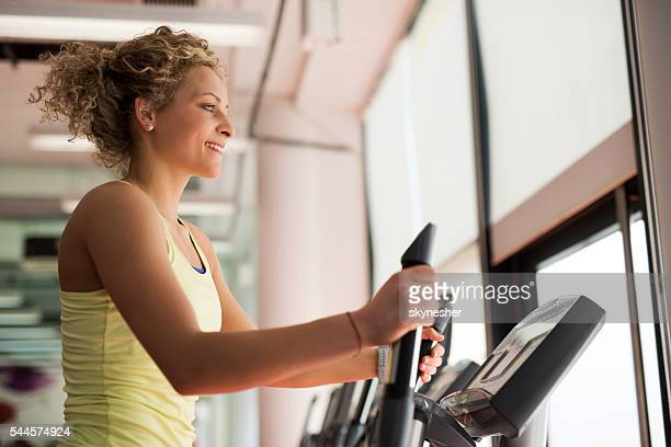 Smiling athletic woman practicing on exercise machine in gym.