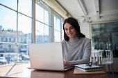 Connected to wireless internet in office, professional administrative manager checking online business report documentation