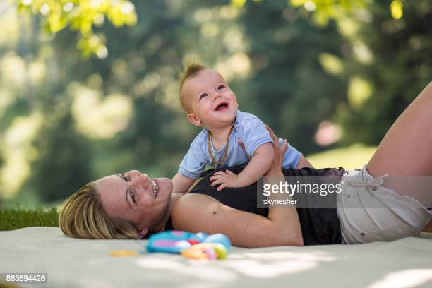 smiling baby boy enjoy his time outdoor with his mom