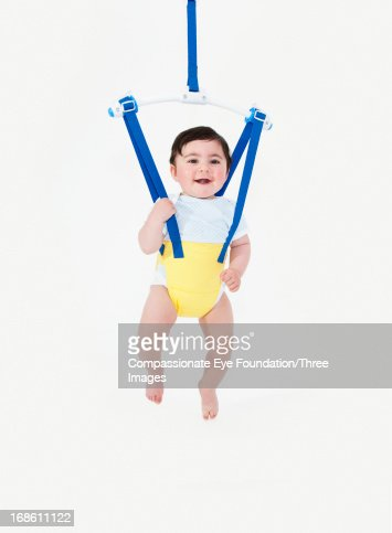 Smiling baby boy in baby bouncer : Stock Photo