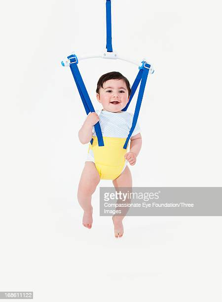 Smiling baby boy in baby bouncer