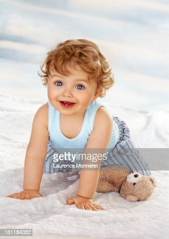 Smiling baby crawling on soft blanket on floor : Stock Photo