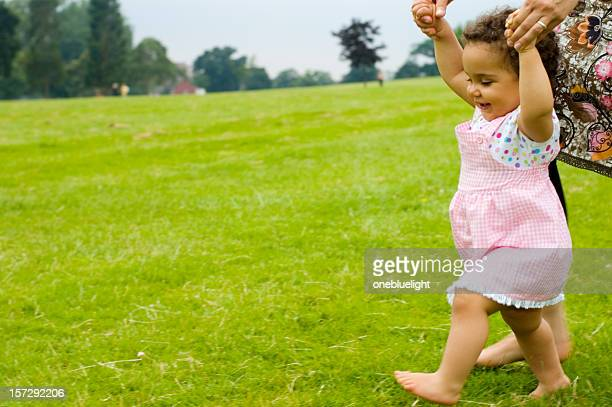 Smiling baby girl learns how to walk on grass with mother