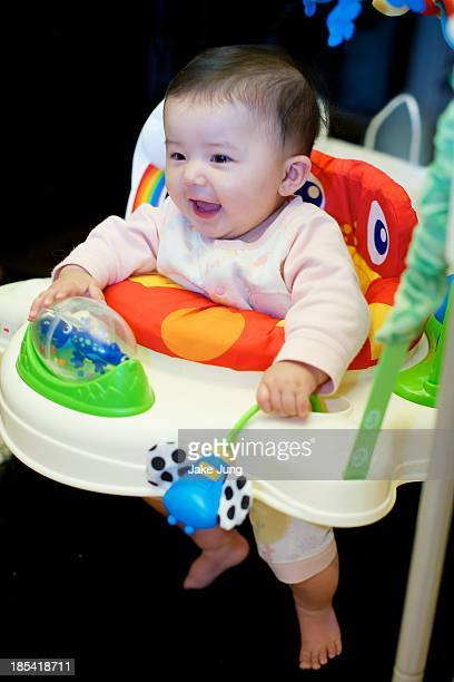 Smiling baby girl playing her baby jumper