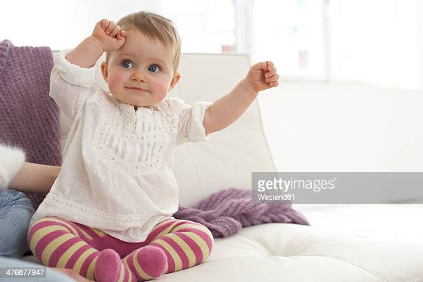 Smiling baby girl with outstrechted arms sitting on sofa