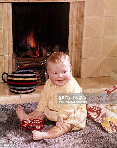A smiling baby in a yellow knit outfit sitting on a rug in front of a fireplace playing with matches in London circa 1960