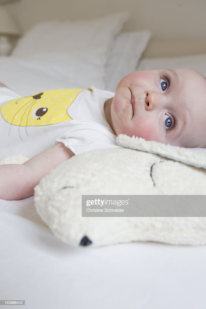 Smiling baby laying on bed : Stock Photo