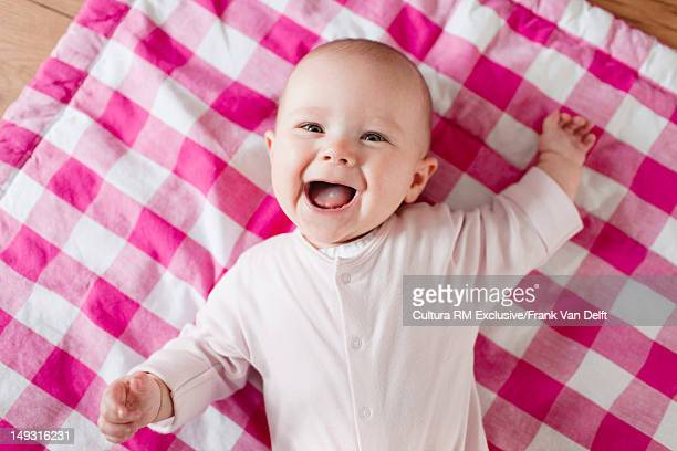 Smiling baby laying on blanket