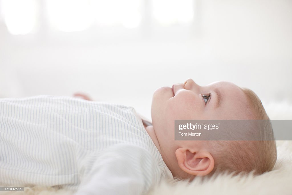 Smiling baby laying on rug : Stock Photo