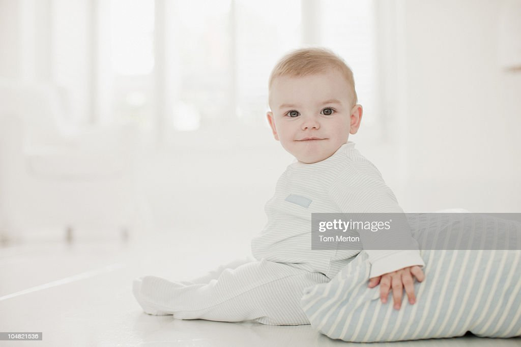 Smiling baby on floor with pillow : Stock Photo