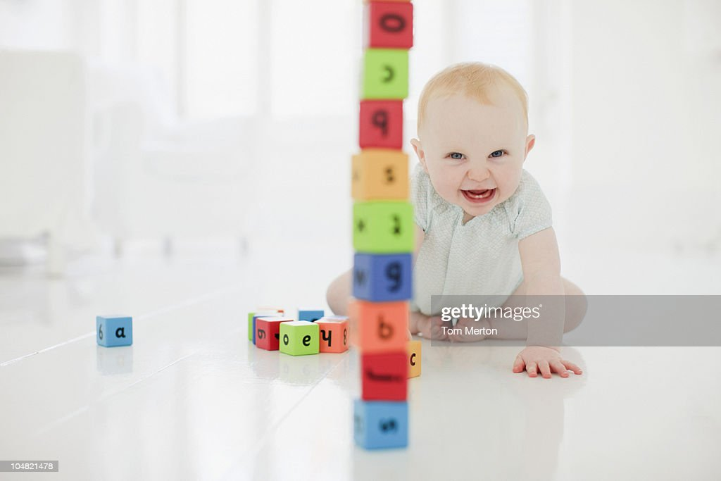 Smiling baby on floor with stacked wood blocks : Stock Photo