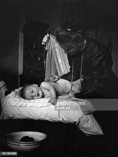 A smiling baby on the diaper changing table in the 1910s