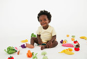 Smiling baby playing with toy fruit