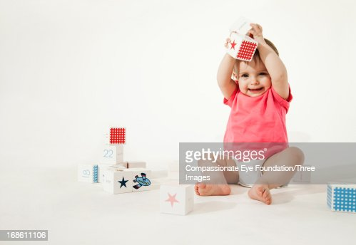 Smiling baby playing with wooden blocks : Stock Photo