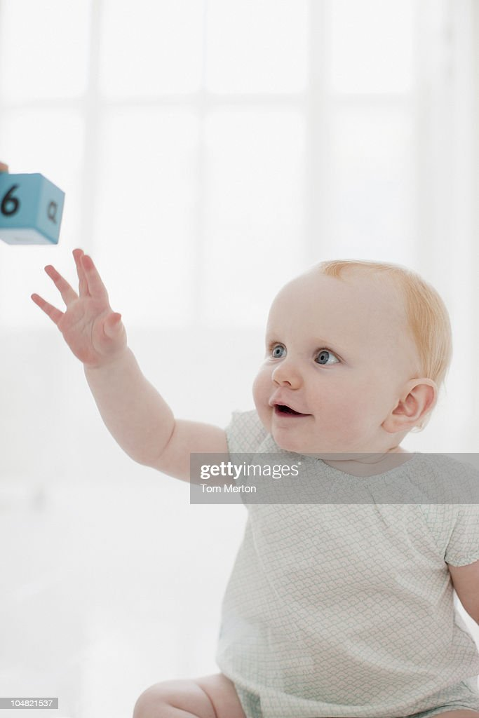 Smiling baby reaching for wood block : Stock Photo