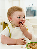 Smiling Baby Sitting in a High Chair Eating a Strawberry