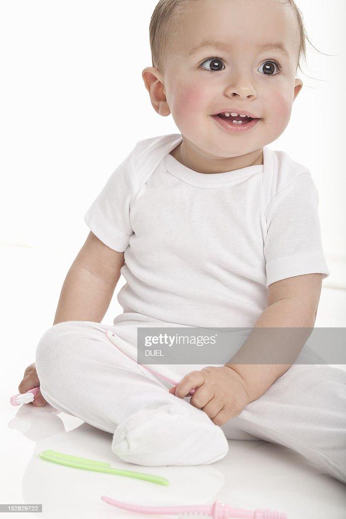 Smiling baby sitting on floor : Stock Photo