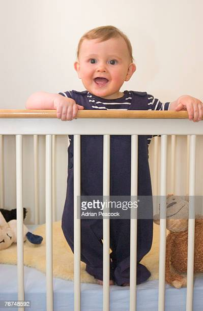 Smiling baby standing in crib