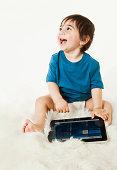 Smiling baby using digital tablet