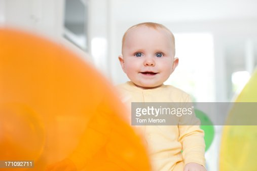Smiling baby with balloons on floor : Stock Photo