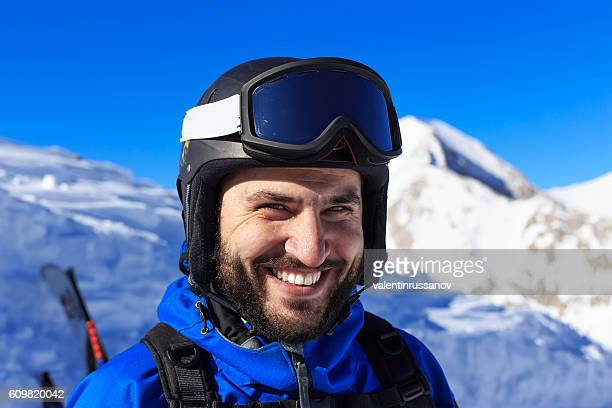Smiling backpacker standing on top of the snow mountain