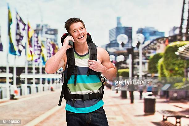 Smiling backpacker talking on phone outdoors
