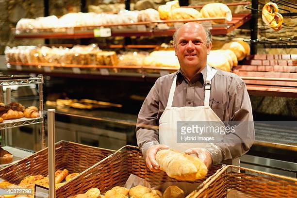 Smiling baker holding loaf of bread